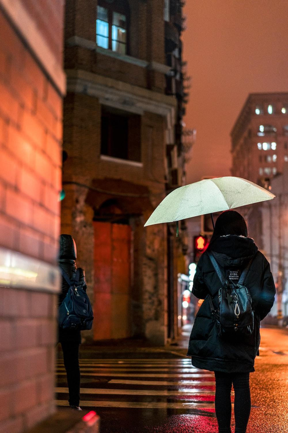 woman walking on sidewalk under umbrella