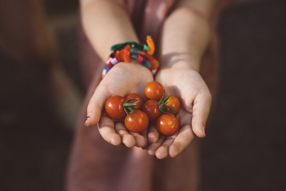 woman with handful of cherry tomatoes