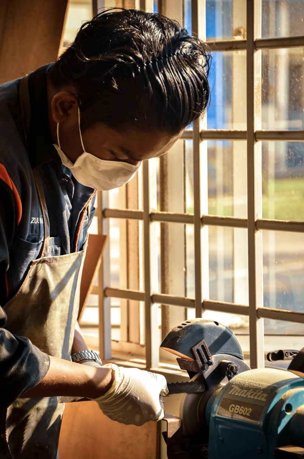 man holding tool sharpen on Makita bench grinder beside window
