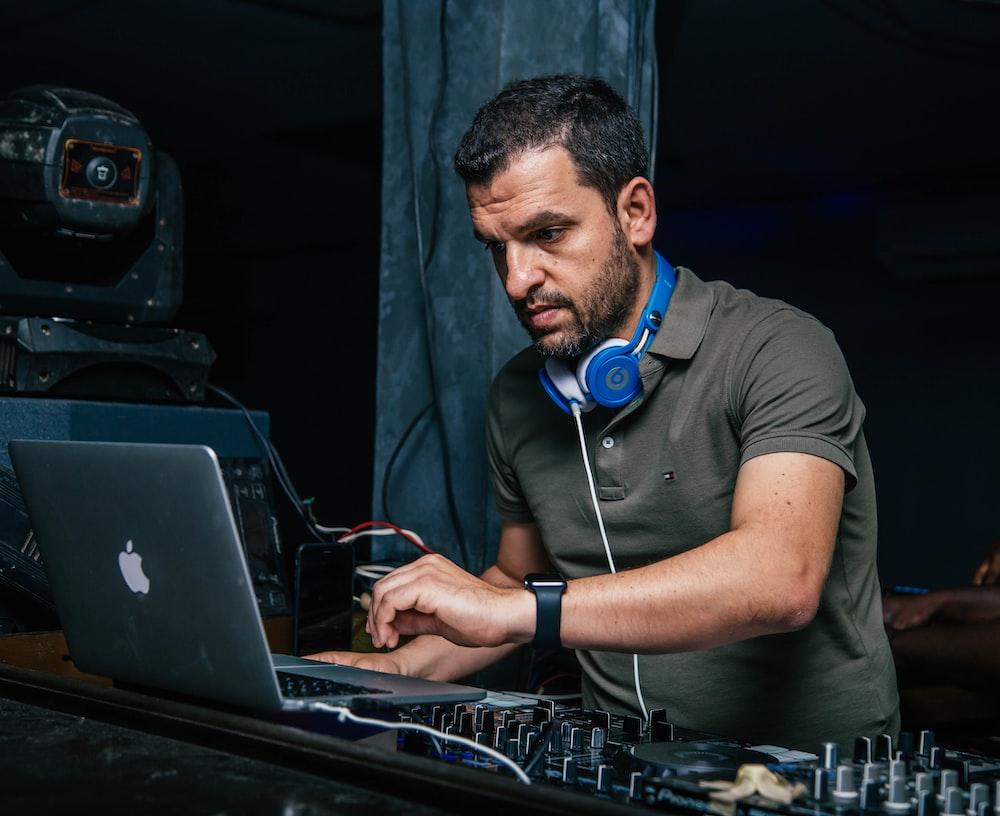 man wearing blue headphones and using MacBook