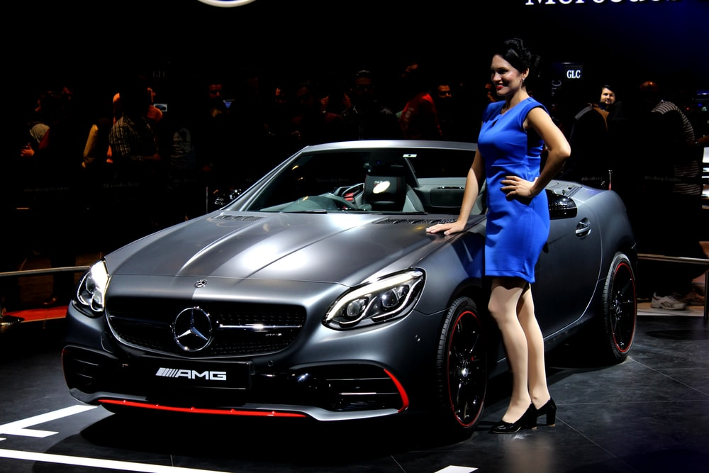woman standing near Mercedes-Benz AMG convertible coupe