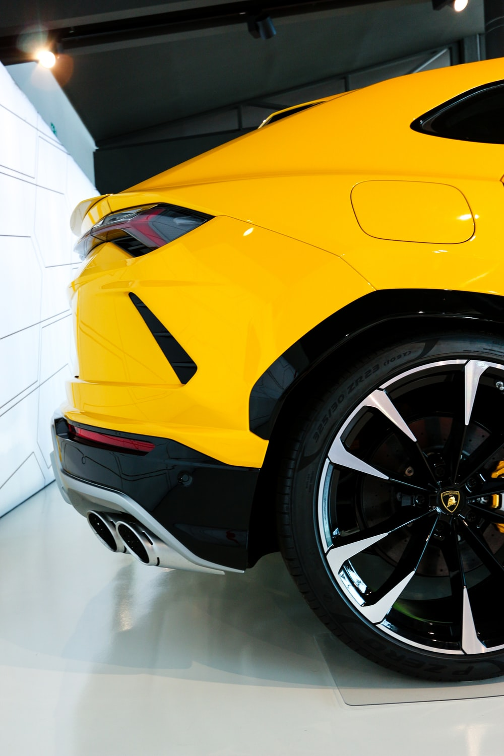yellow vehicle parked beside wall