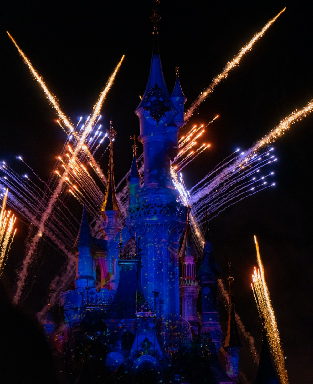time-lapse photography of fireworks shooting above Disneyland castle