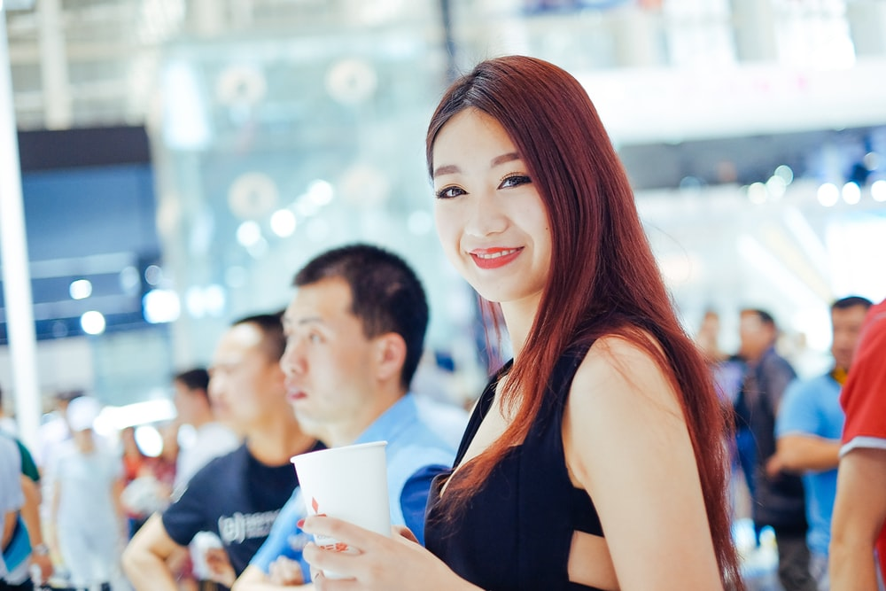 selective focus photography of smiling woman holding white cup