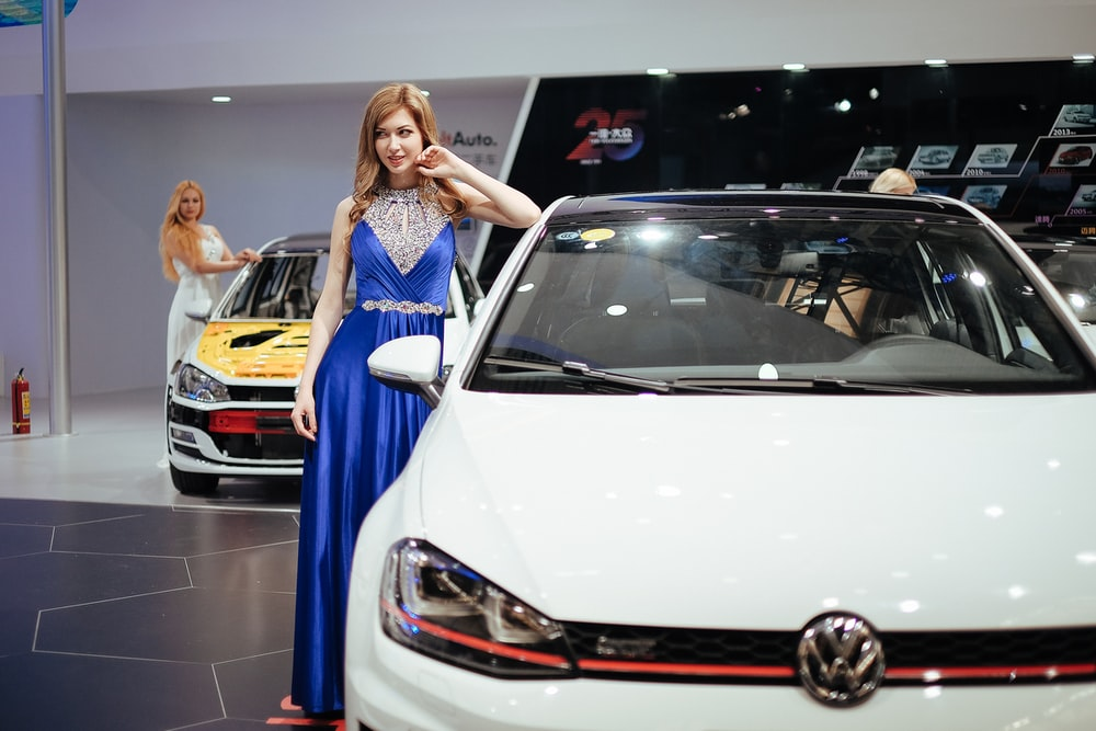 woman stands near Volkswagen car