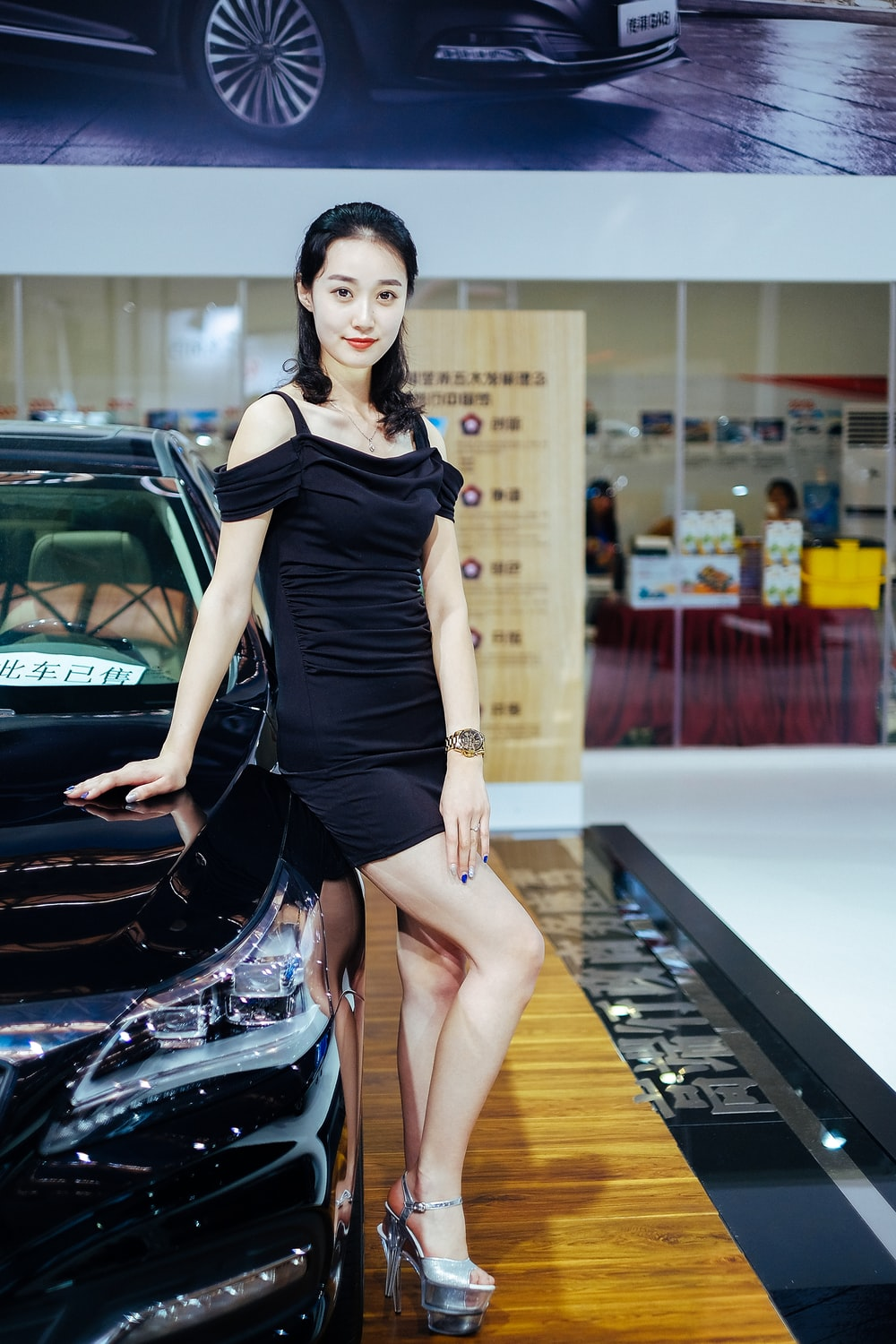 woman in black cold-shoulder dress standing beside parked car