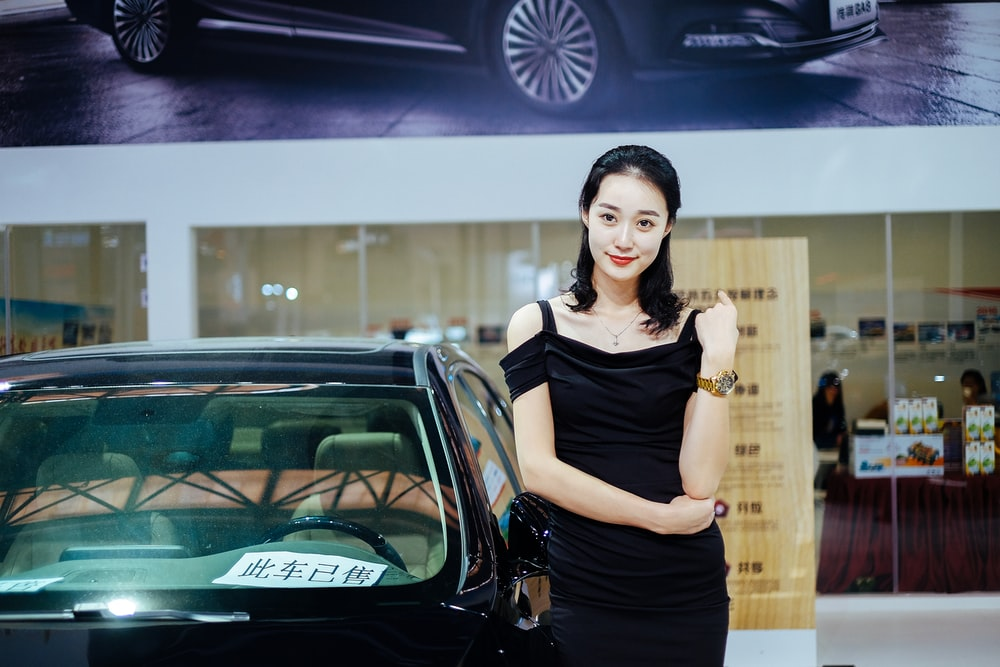woman stands near black car