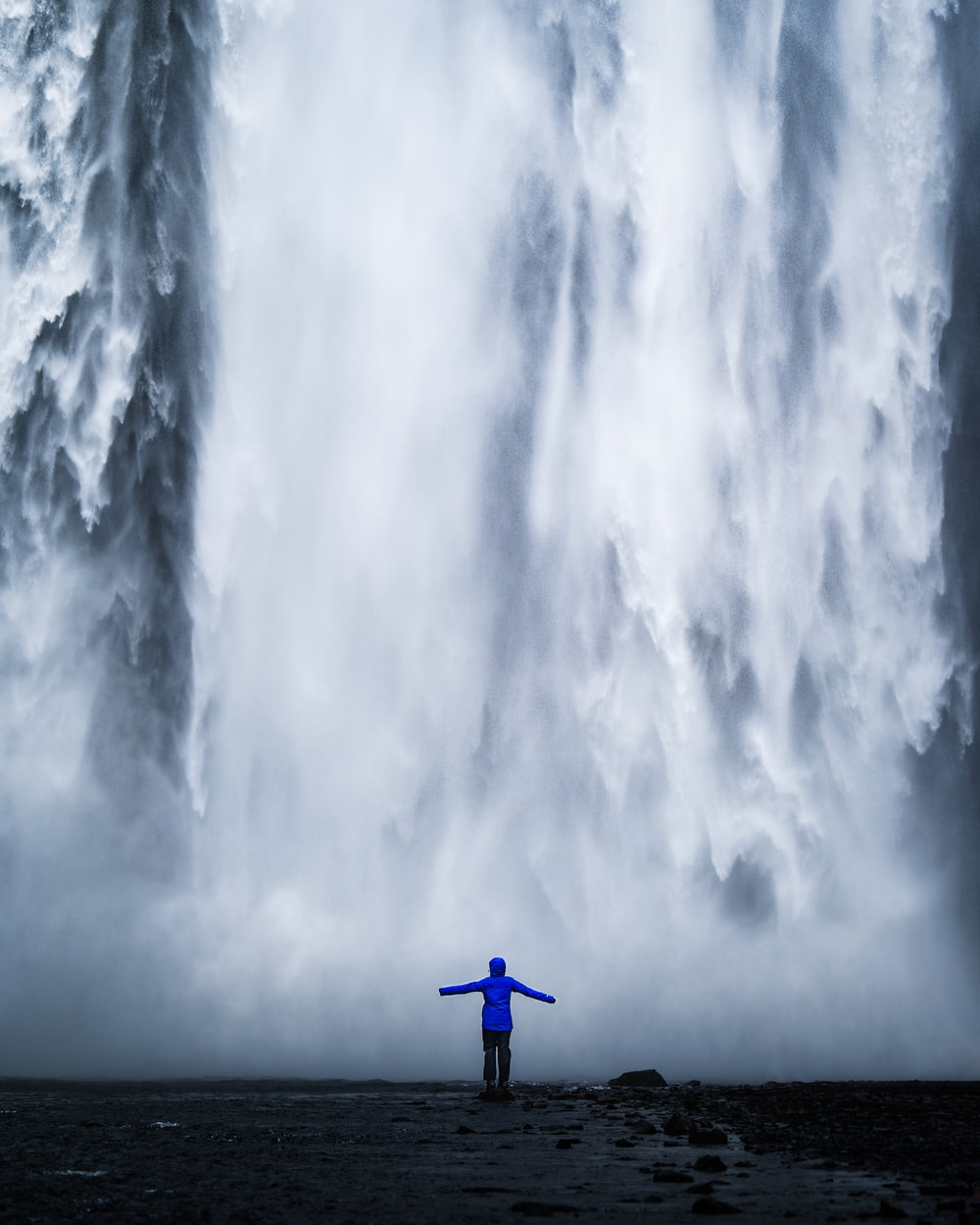 person wearing blue jacket standing in front of waterfalls