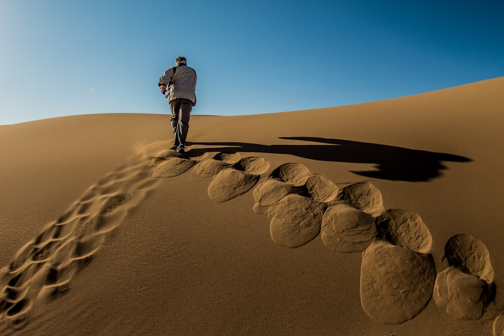 man waking on brown sand dunes