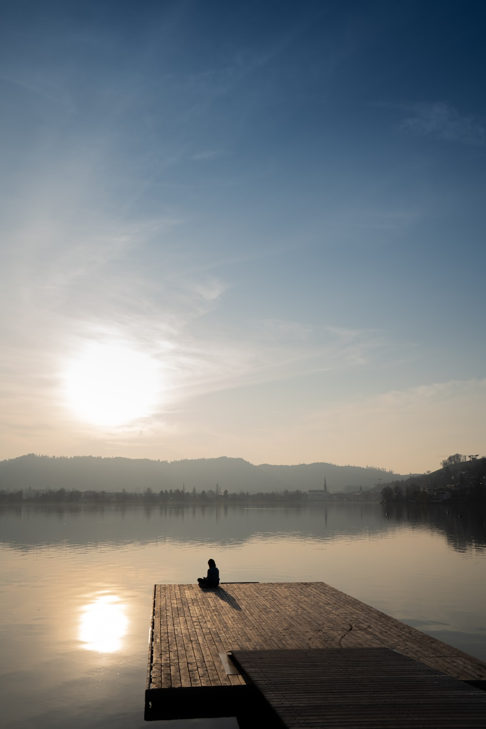 person sitting on wooden dock