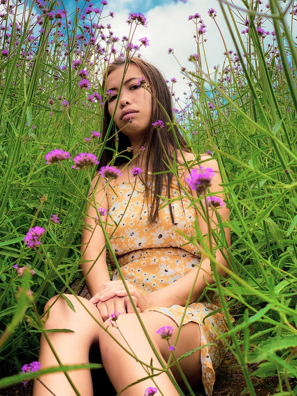 woman sitting on ground surrounded by purple-petaled flowers