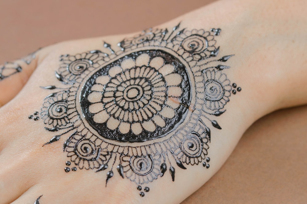 person in black floral mendhi tattoo