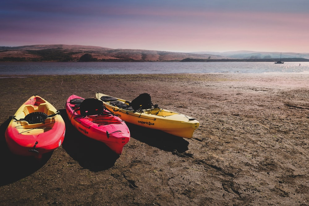 two red and one yellow kayaks near shore