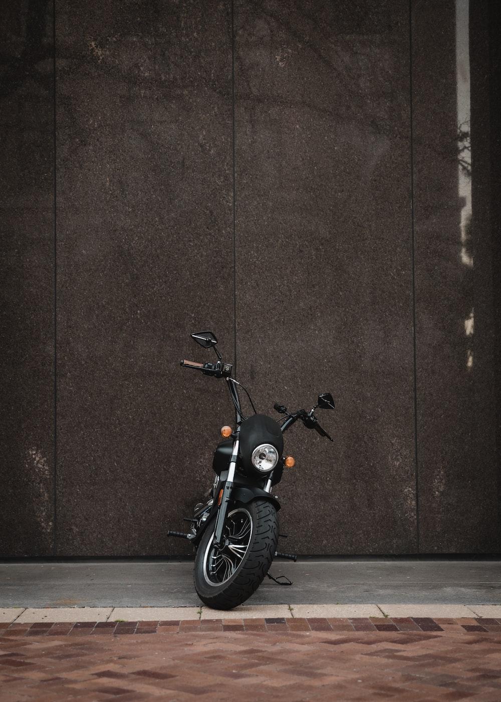 black underbone motorcycle beside wall