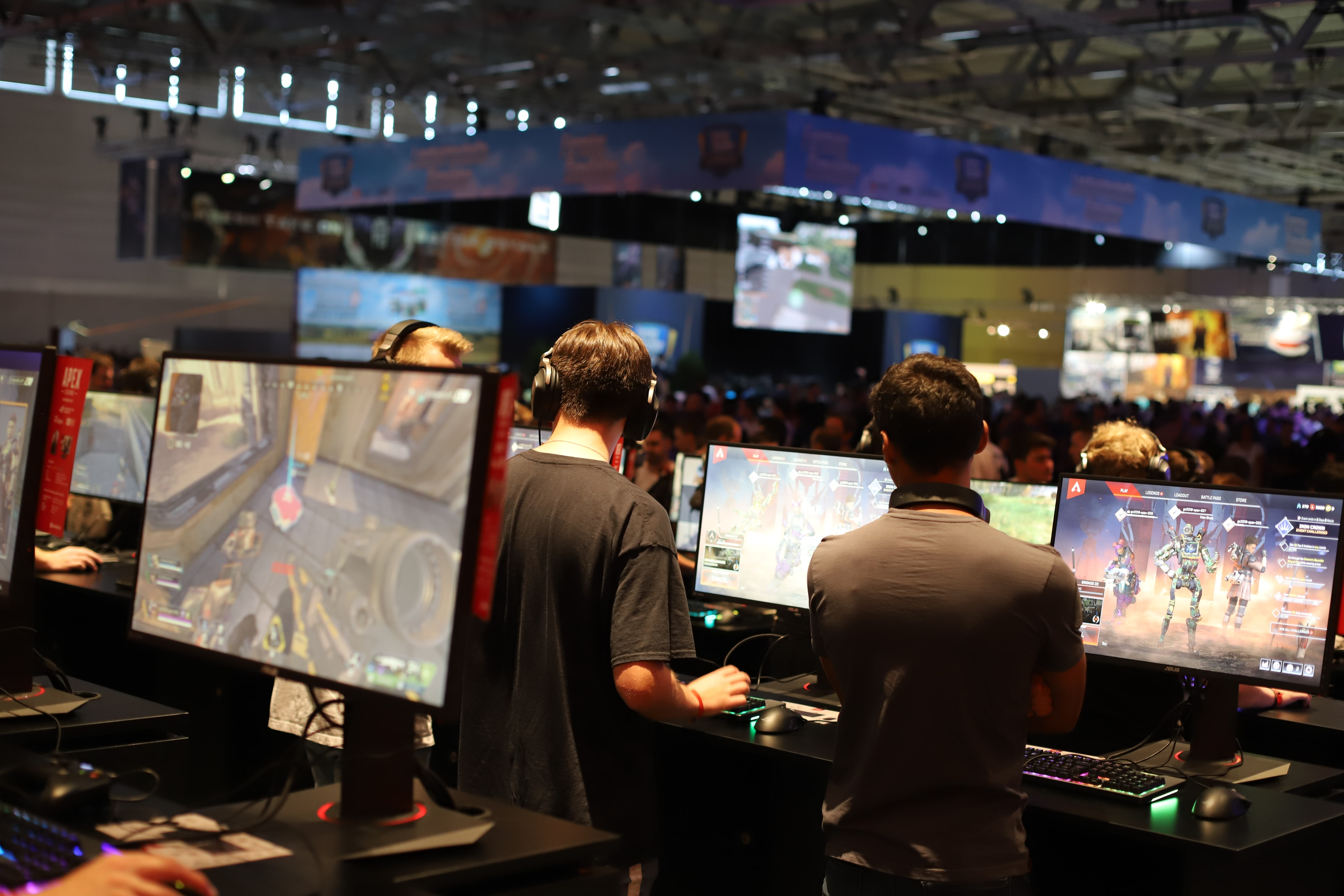 A hall filled of people playing video games on multiple monitors