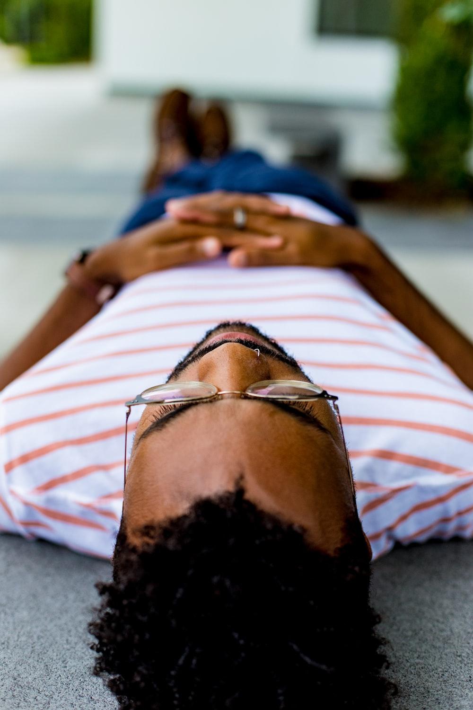 man wearing eyeglasses lying on concrete pavement
