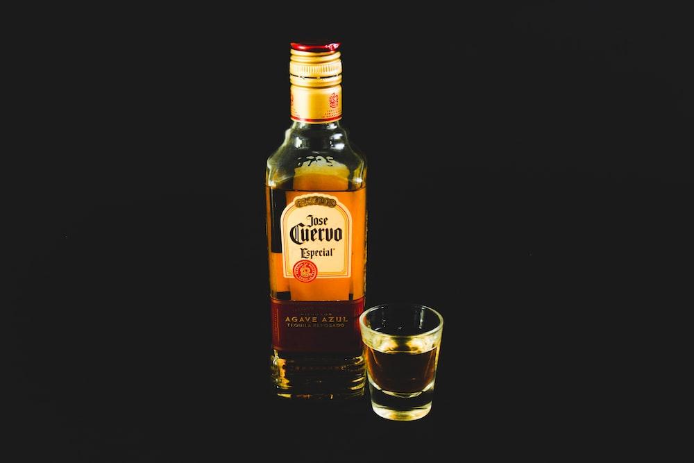 labeled bottle beside short glass