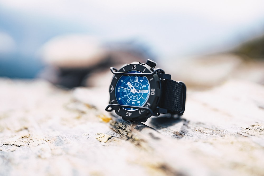 blue and white analog watch with black straps