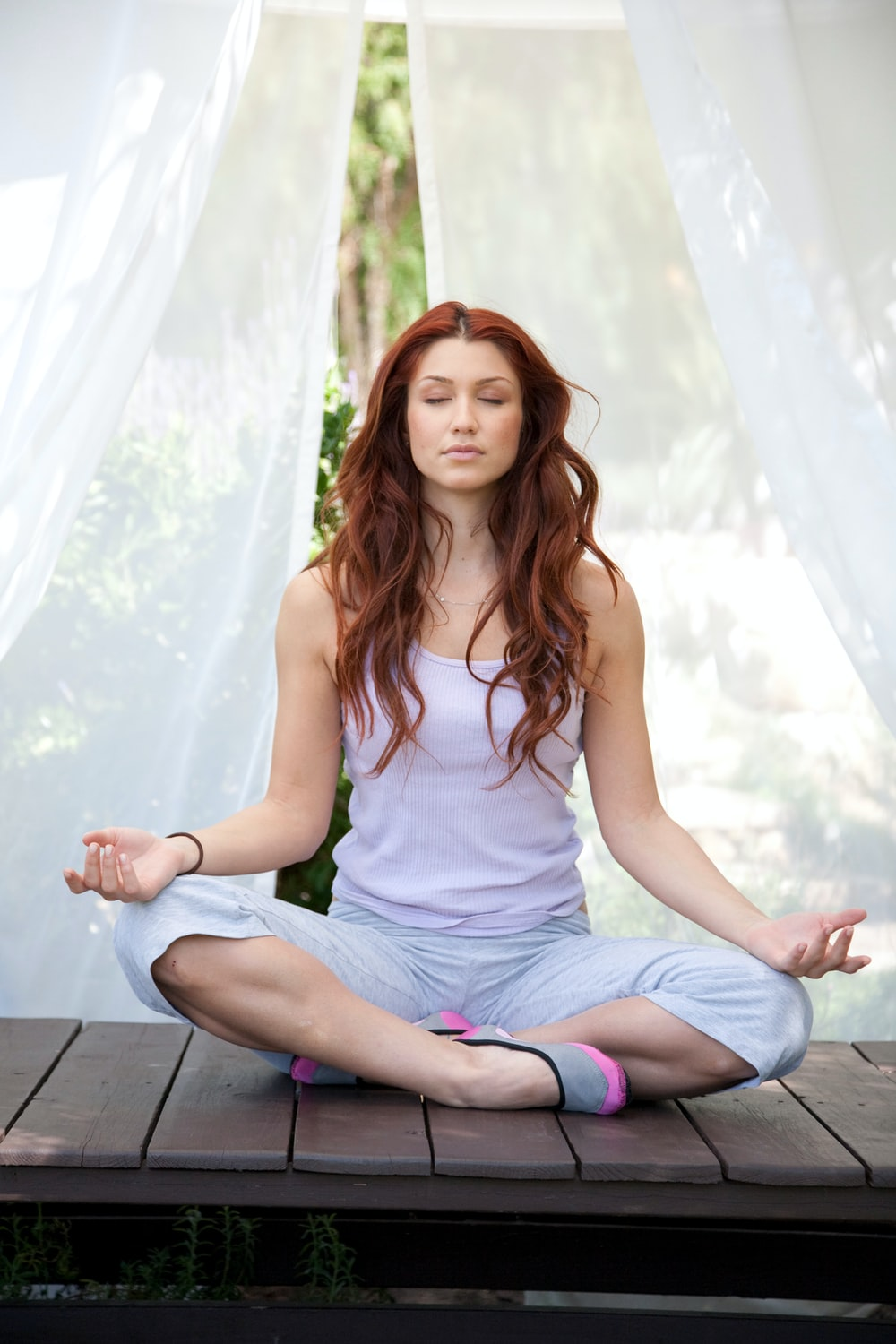 woman doing yoga pose sitting on wooden ground