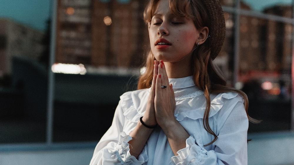 woman in white top praying