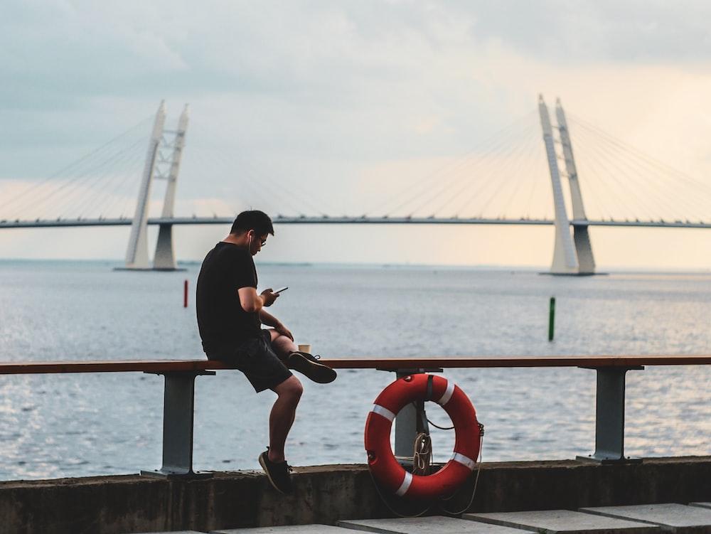 man browsing smartphone sitting near water