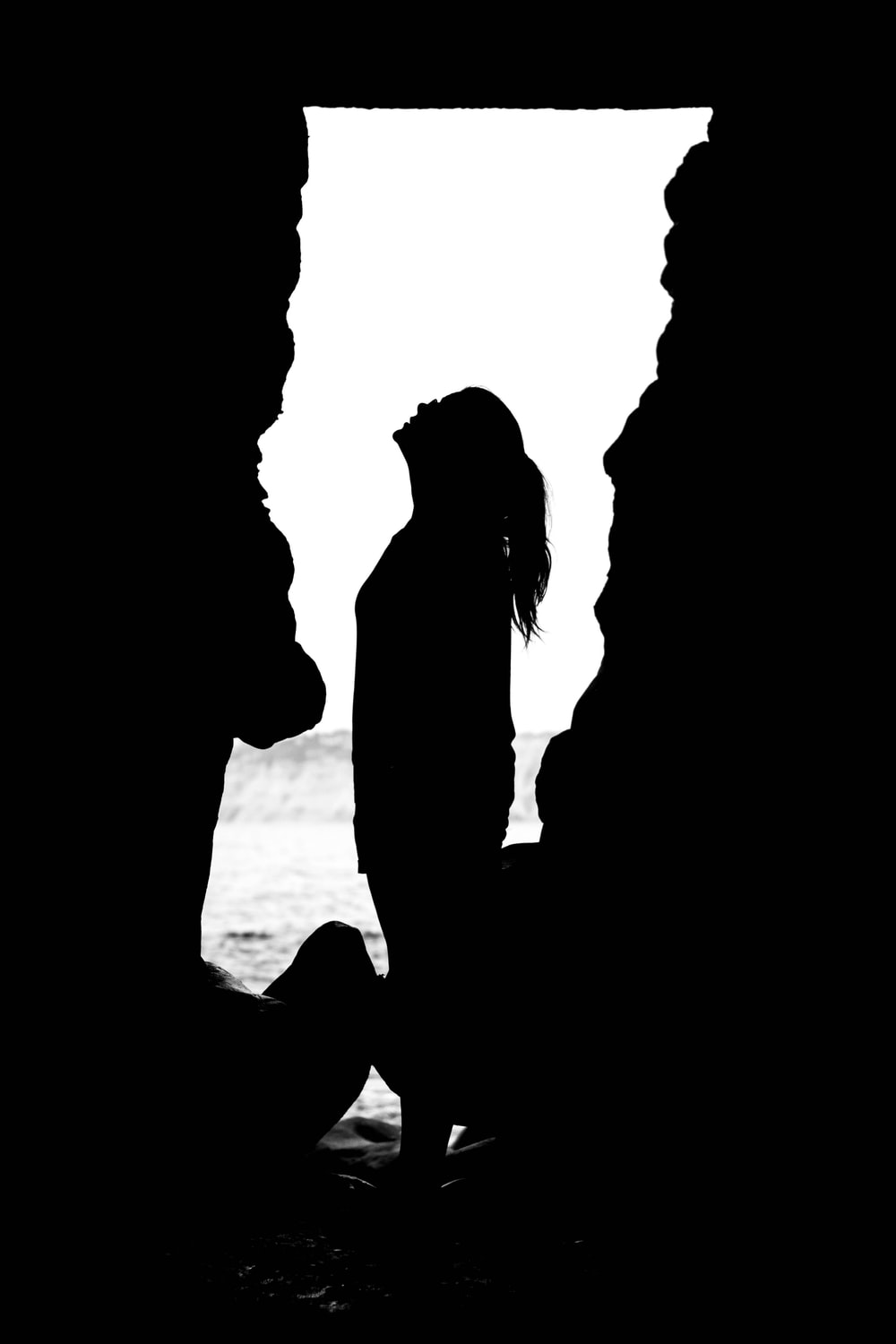 silhouette of woman looking up inside cave