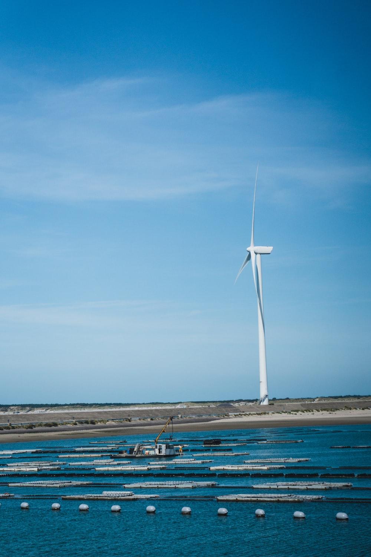 white wind turbine beside sea
