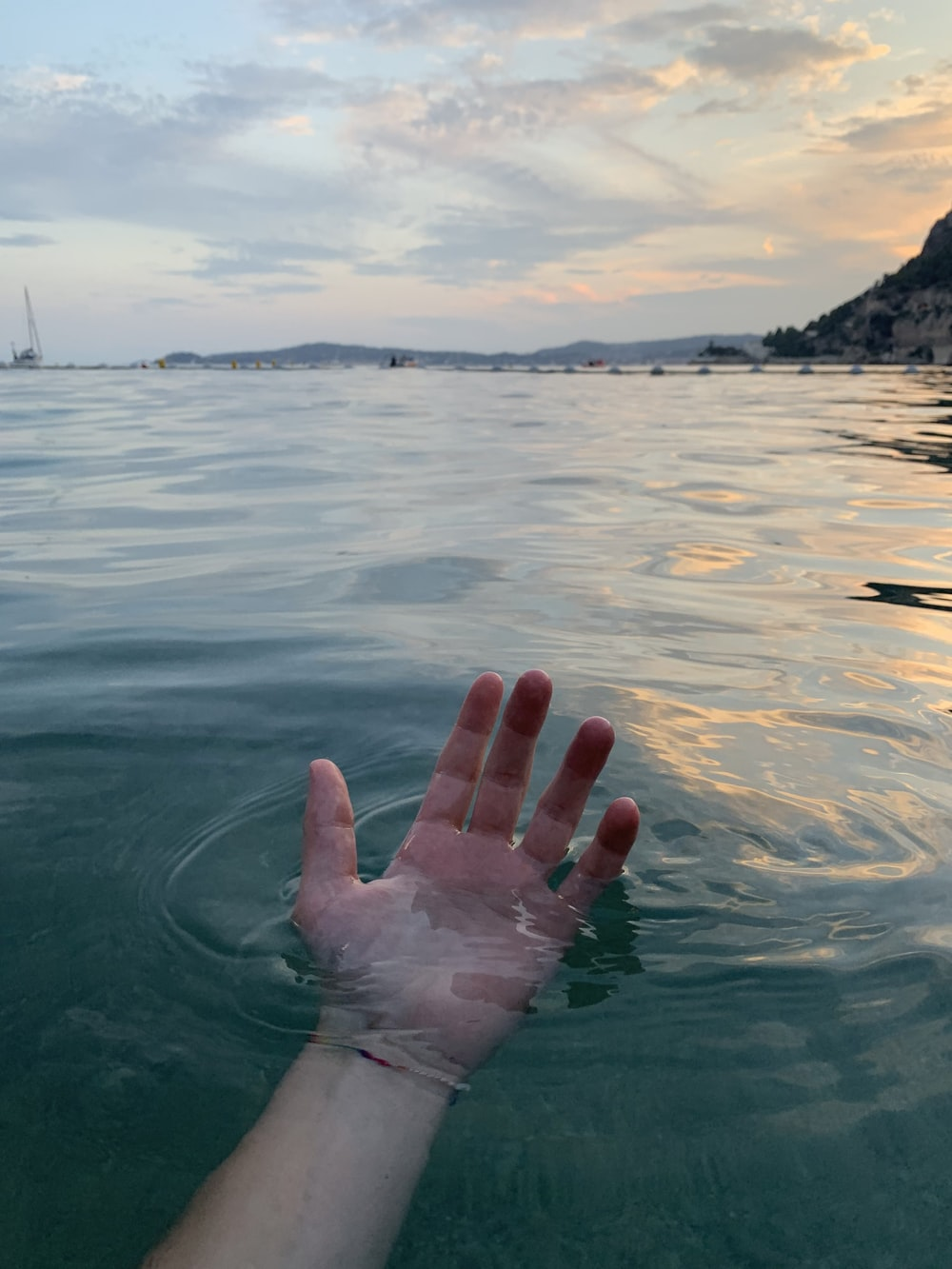 person hand on water at daytime