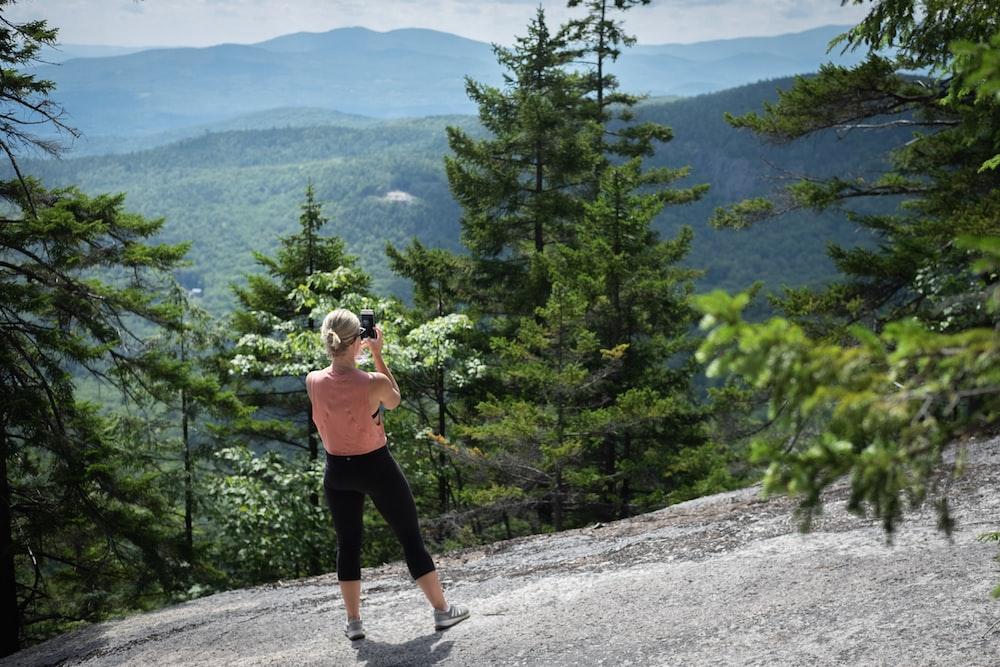 woman standing on rock near trees