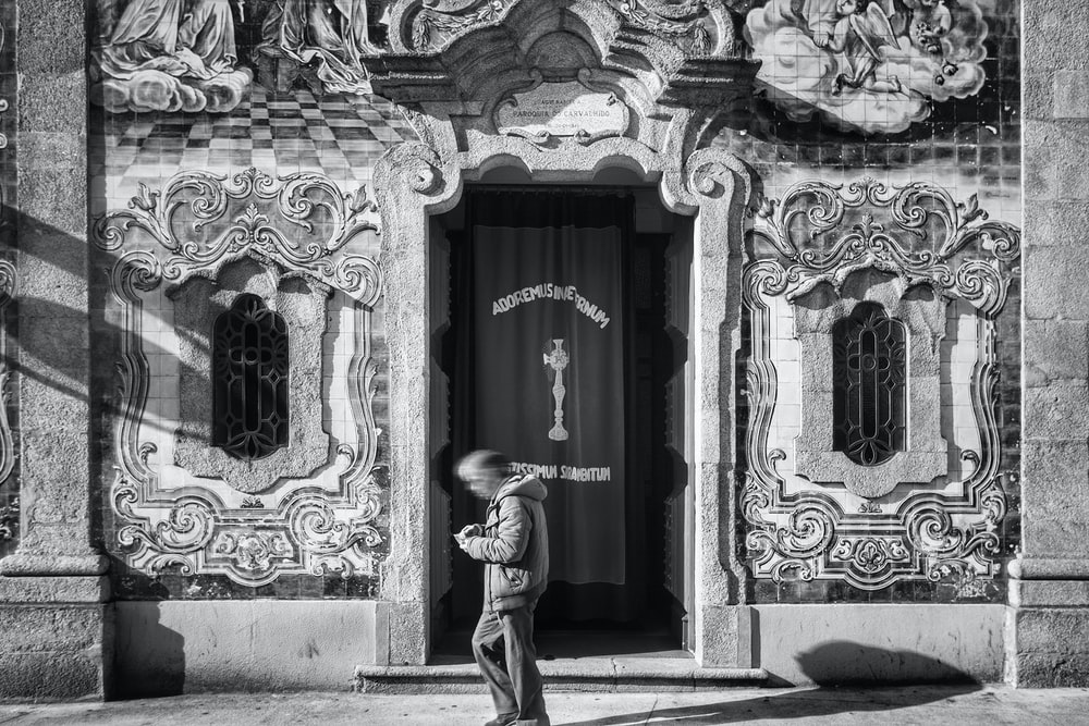 grayscale photo of man walking near wall