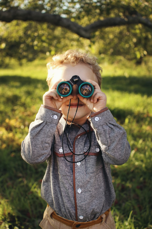child standing while using green binoculars