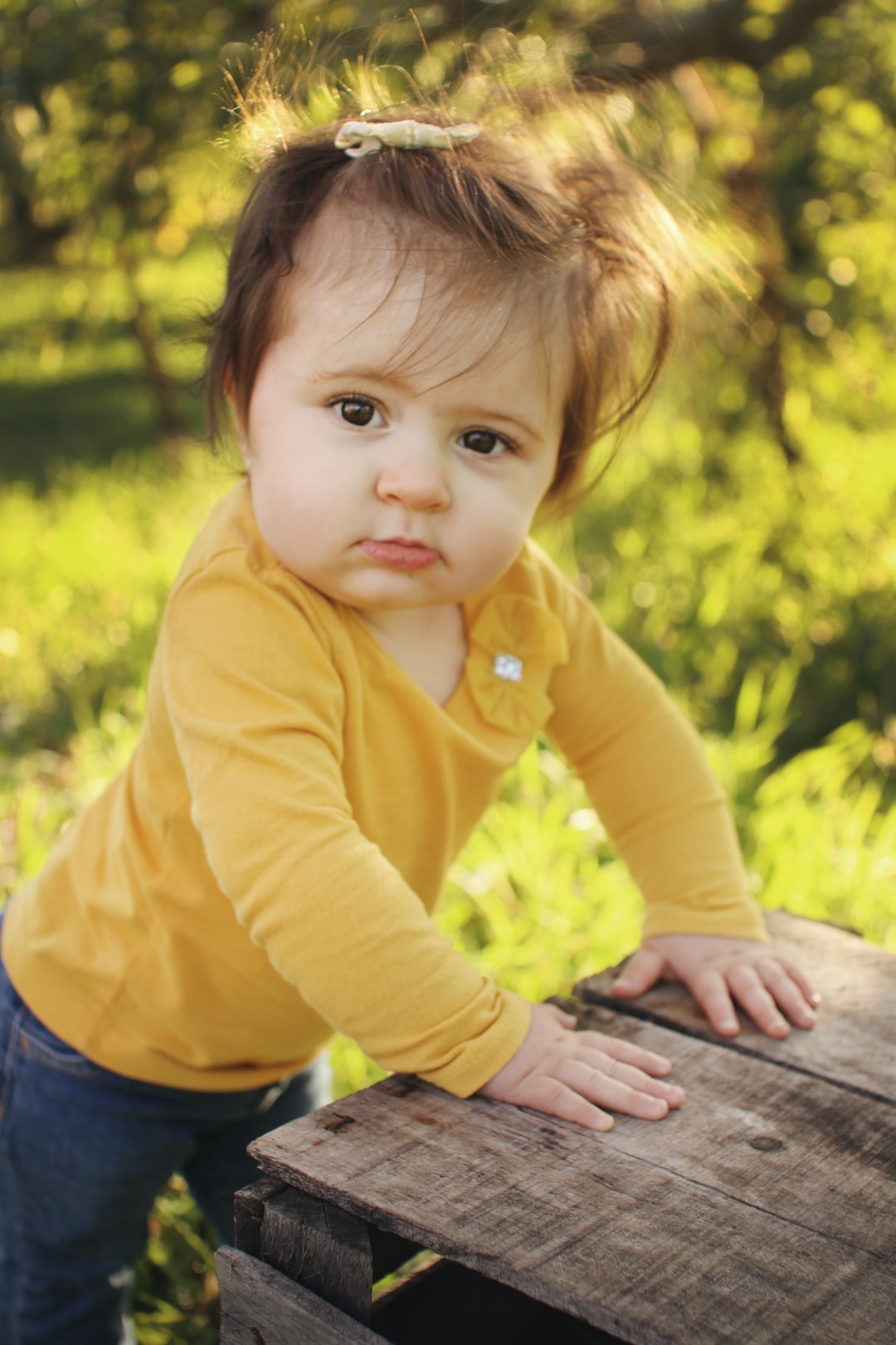 Young toddler girl wearing yellow shirt with red hair standing against a wooden crate in apple orchard at golden hour.