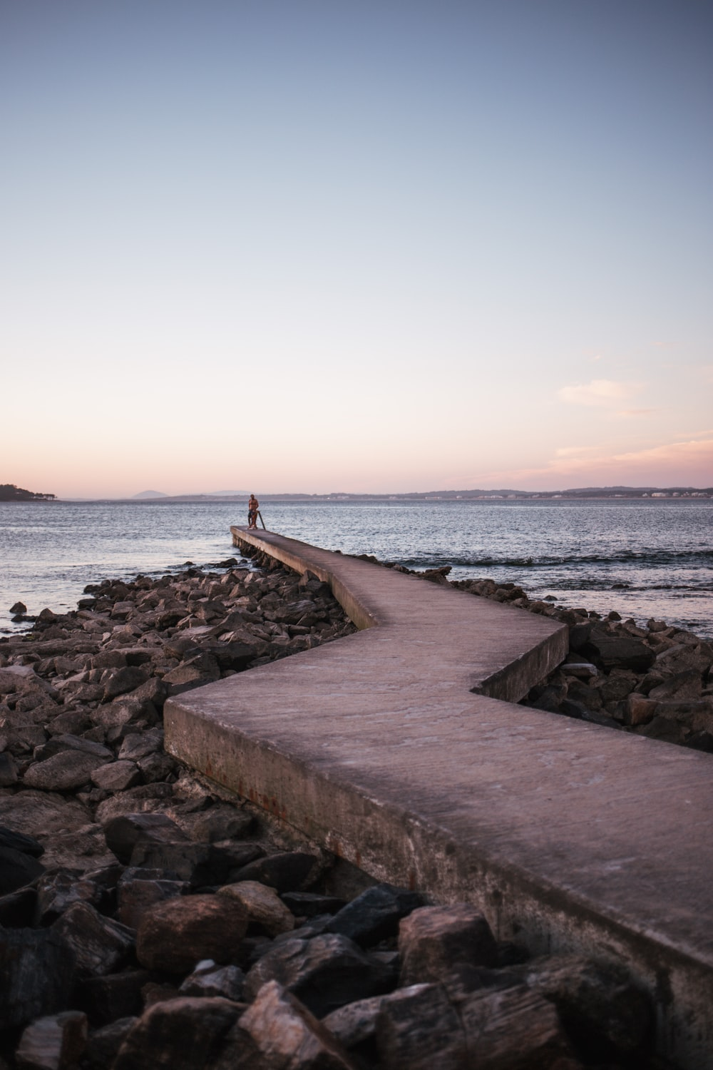 concrete pathway on rocky shore during day