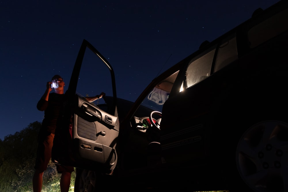 A man beside a parked car with a dead battery at night on the phone with support