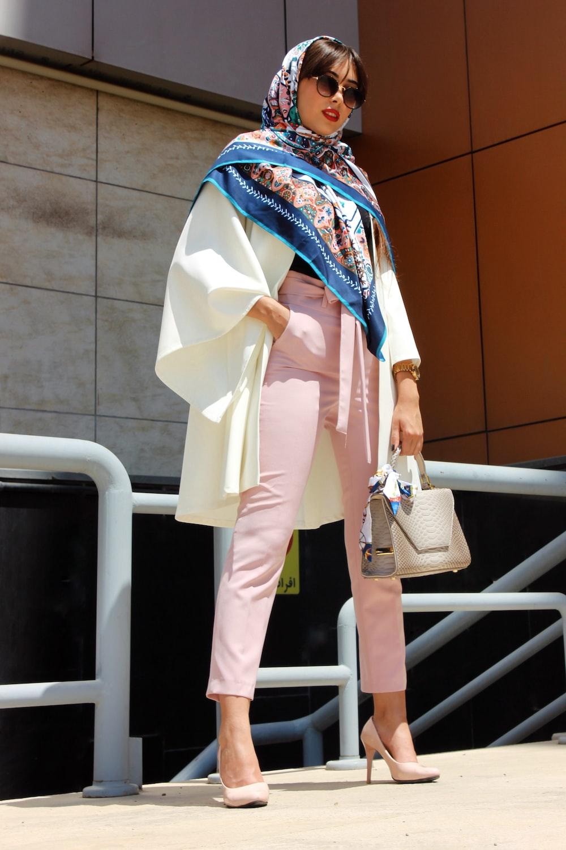 woman wearing pink pants holding grey leather handbag