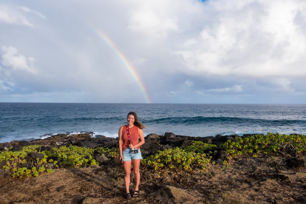 woman standing in front of body of water and rainbow