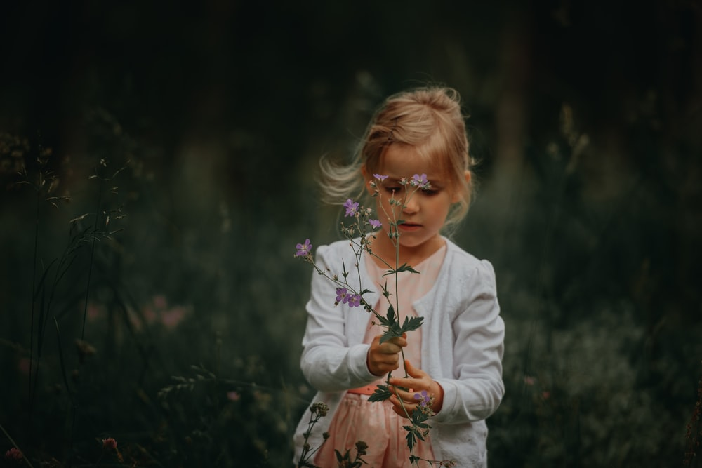 selective-focus photography of girl holding flower