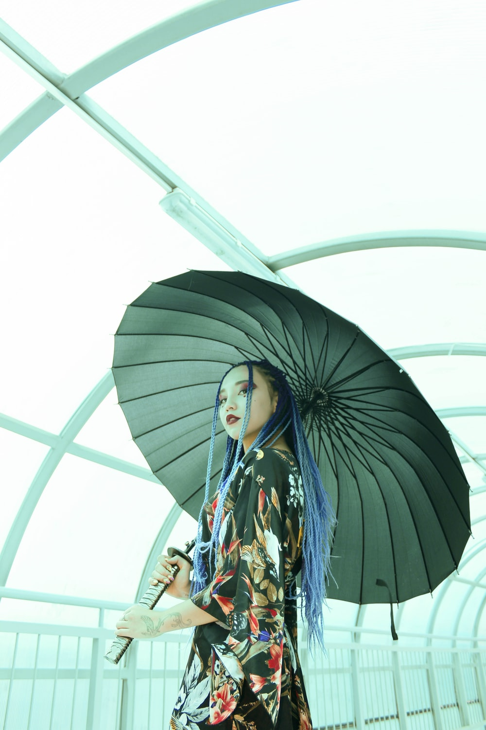 woman holding umbrella inside shed