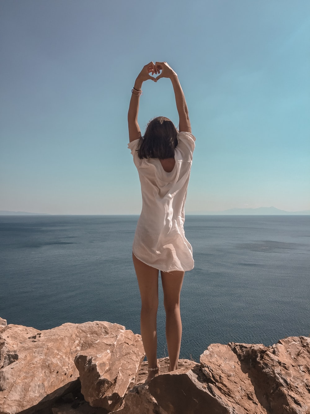 woman raising hands standing on cliff at daytime
