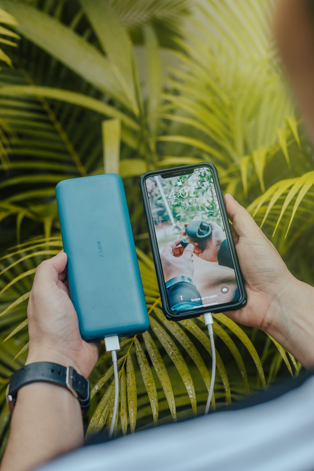 black smartphone and green powerbank close-up photography