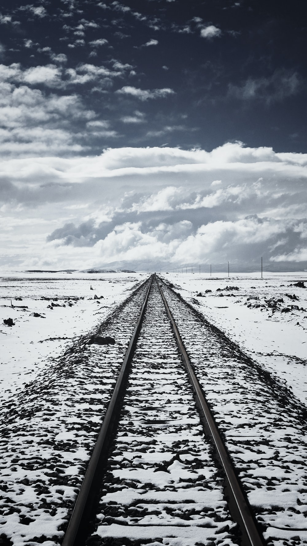 snow covered train rail under cloudy sky