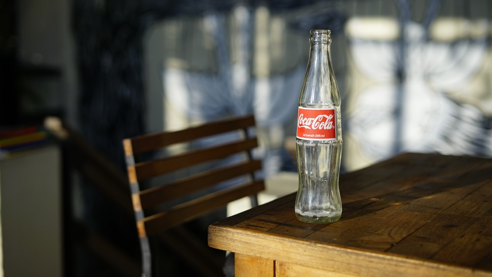red Coca Cola glass bottle on table