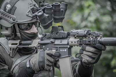 person holding grey and black rifle army zoom background