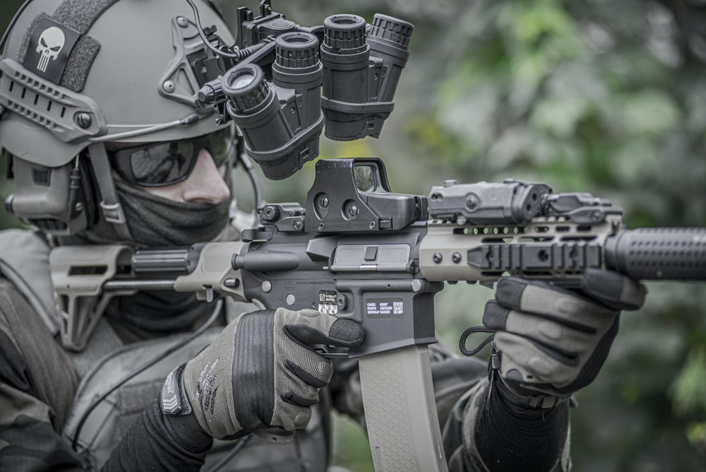 person holding grey and black rifle