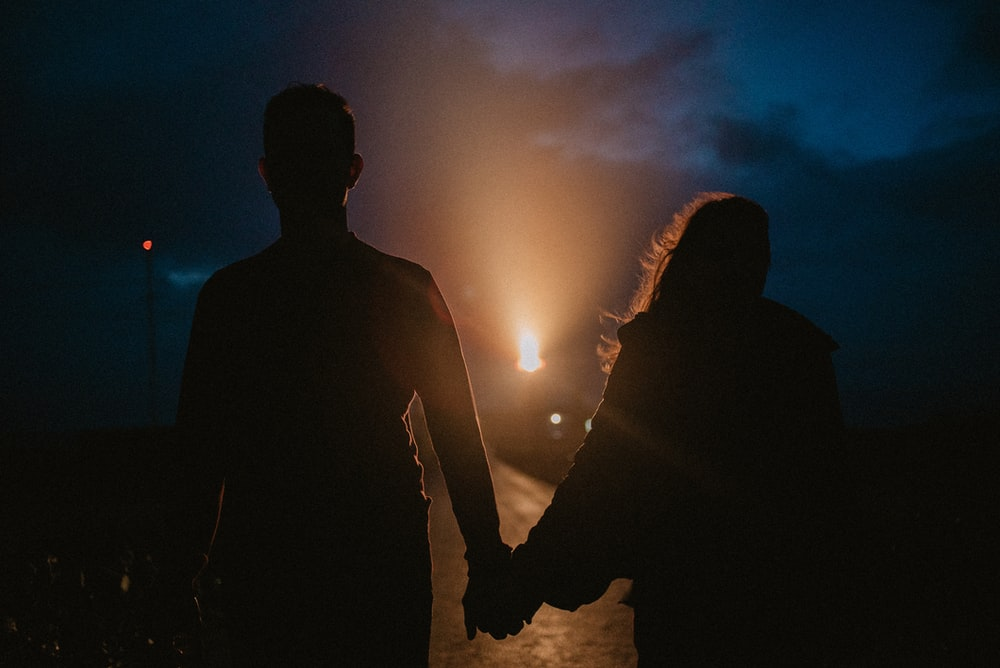 gray-scale photo of man and woman holding hands