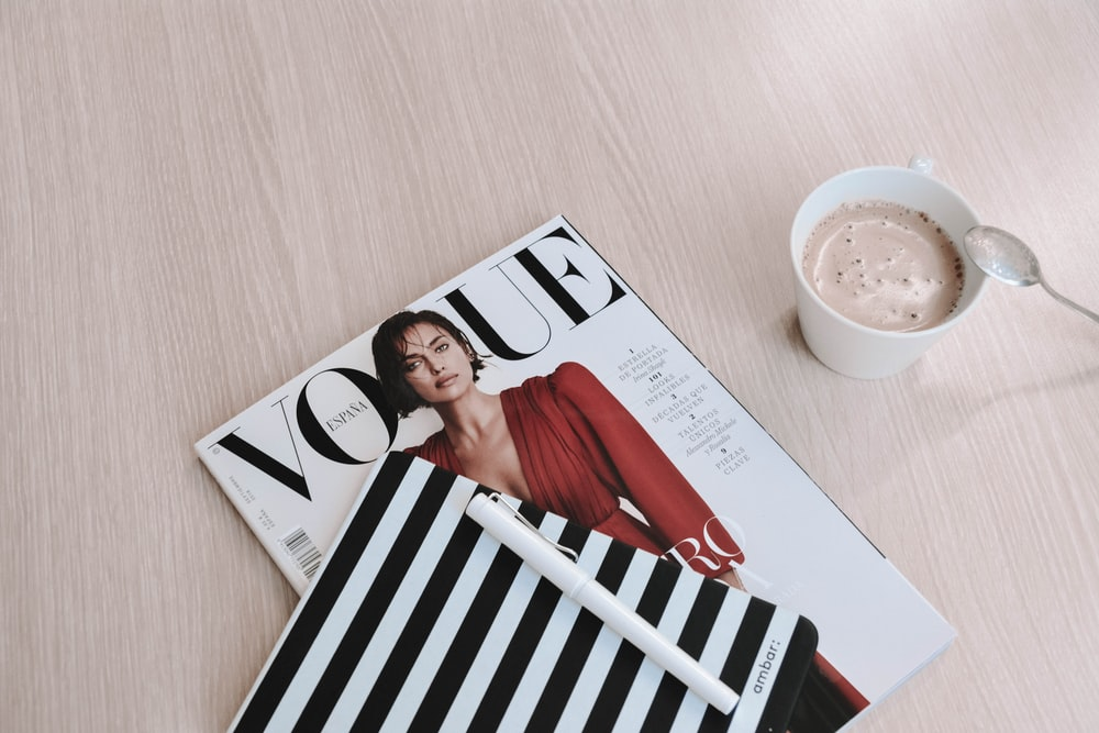 white capped pen on top of Vogue magazine beside cup of coffee