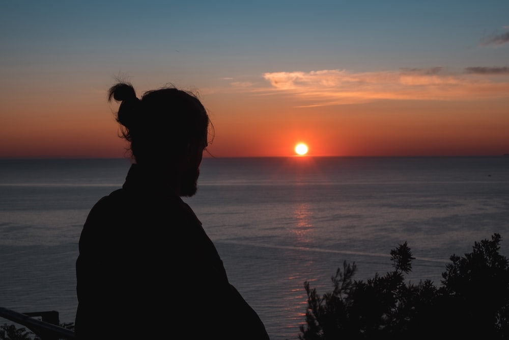 silhouette of man watching golden hour