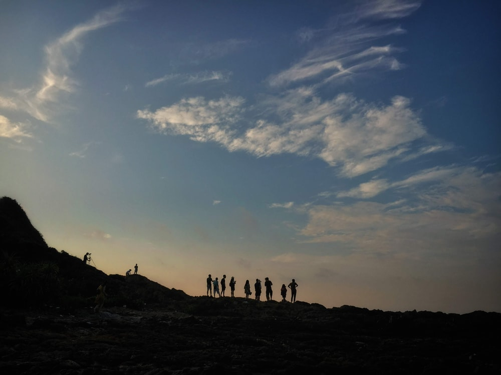 silhouette of people hiking on slope