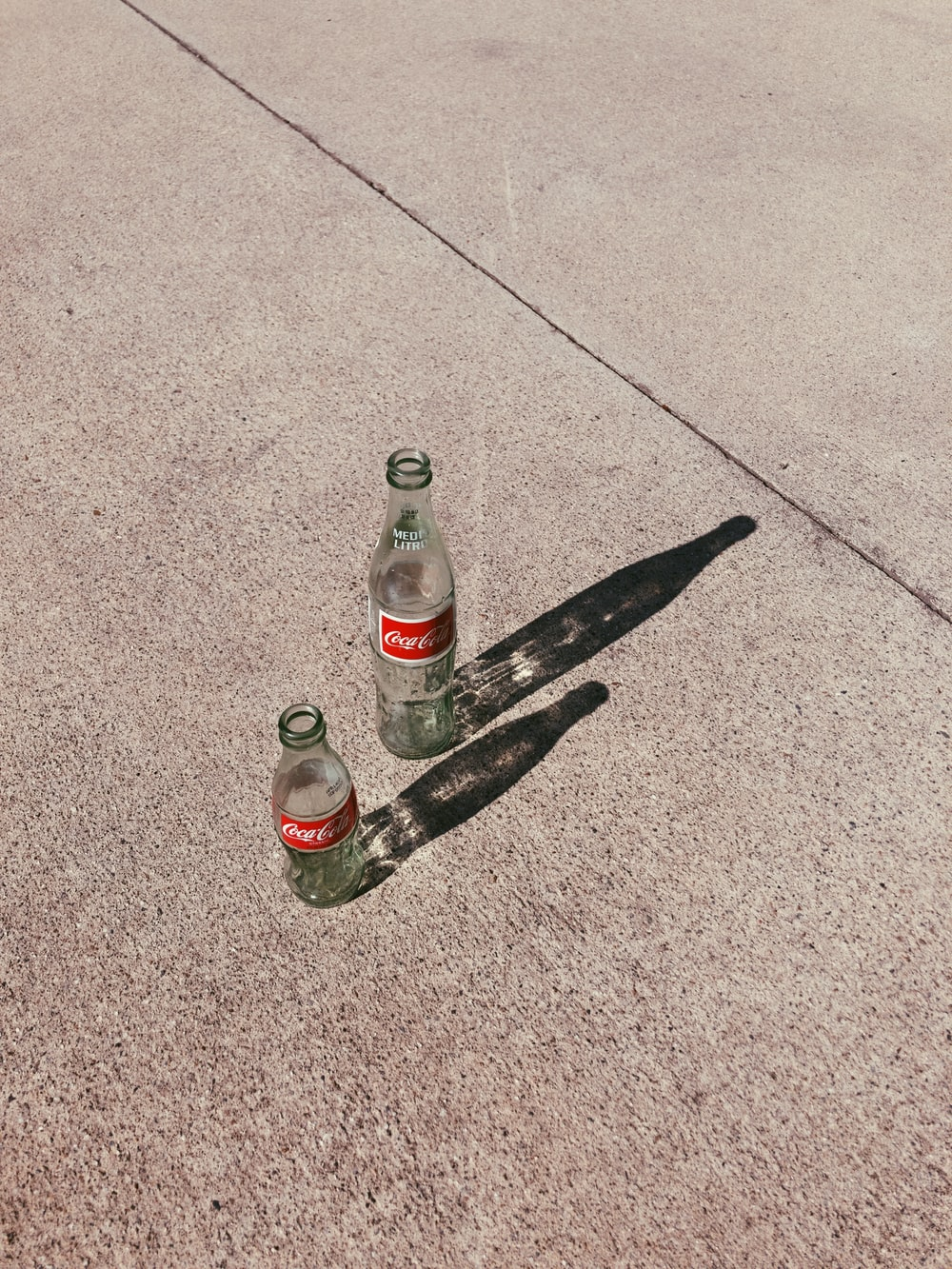 two empty glass bottles on pavement