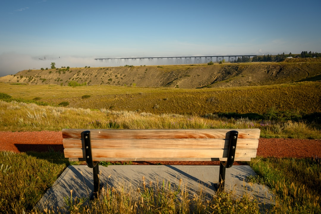 A bench overlooking the Oldman River Valley with a view of the High Level Bridge engulfed in fog.